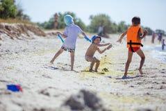 投掷沙子的两个更老的男孩一致更加年轻 库存图片