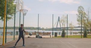 投掷球入箍和庆祝与的运动的可爱的非裔美国人的男性篮球运动员画象  股票录像