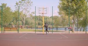 投掷球的年轻活跃非裔美国人的男性篮球运动员特写镜头画象入的箍户外 股票视频