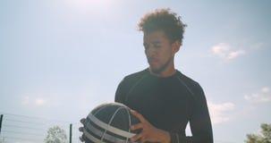 投掷球的年轻熟练的非裔美国人的男性篮球运动员特写镜头画象入箍户外 影视素材
