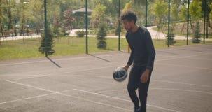 投掷球的年轻英俊的非裔美国人的男性篮球运动员特写镜头画象入的箍户外 股票录像