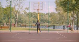 投掷球的年轻英俊的非裔美国人的男性篮球运动员画象入在法院的一个箍在都市 股票录像