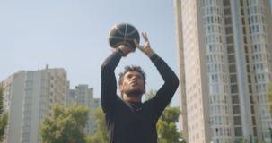 投掷球的年轻运动的非裔美国人的男性篮球运动员特写镜头画象入的箍户外 股票录像