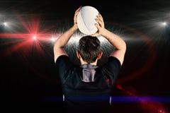 投掷球的被转动的橄榄球球员的综合图象 免版税库存照片