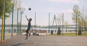 投掷球的运动的可爱的非裔美国人的男性篮球运动员画象入在法院的一个箍在 股票视频