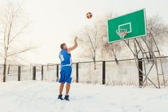 投掷篮球球的蓝色制服的蓝球运动员入在一个街道篮球场的篮子在冬天 免版税库存照片