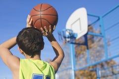 投掷篮球的少年入箍 免版税库存图片