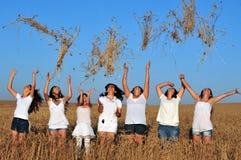 投掷麦子的愉快的年轻以色列妇女对在Shavuot J的空气 免版税库存照片