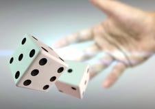 投掷2个模子的手在有后边透镜火光的赌博娱乐场 免版税库存照片