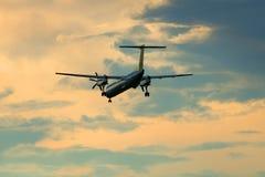投炸弹者破折号8-Q402 (YL-BAI)航空公司宣扬在暮色天空的波儿地克的飞行 库存图片