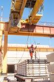 投石者接受板材在吊车司机 图库摄影
