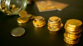 投资的标志,保留金钱概念 随着金币的增加专栏的特写镜头静物画在黑桌上的 股票视频