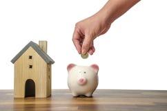 投资者手举行与救球的一枚硬币在家庭模型的金钱上把放的存钱罐中家庭背景的, 免版税库存照片