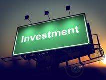 投资-在日出背景的广告牌。 免版税图库摄影