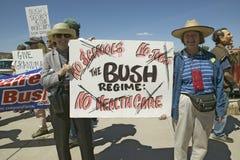 抗议的抗议者在图森乔治・ W.拿着符号的布什总统亚利桑那他的伊拉克对外政策 拿着标志的布什抗议他的医疗保健计划 免版税库存图片