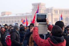 抗议者使用一种片剂拍摄抗议 免版税库存图片