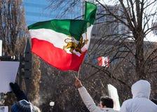 抗议者在多伦多,加拿大骄傲地挥动伊朗前革命旗子 免版税库存照片