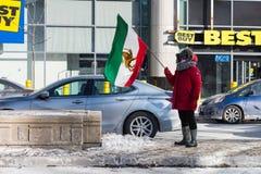 抗议者在多伦多,加拿大骄傲地挥动伊朗前革命旗子 库存照片