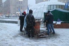 抗议者在酒桶附近取暖 免版税库存照片
