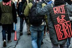 抗议者的后面的特写镜头佩带标志的 库存图片