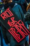 抗议者的后面的特写镜头佩带标志说的 库存图片