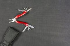 折叠为钓鱼者的红色多功能工具 免版税库存图片