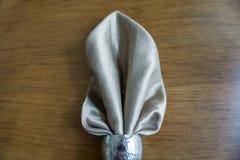 折叠在三角的金黄餐巾典雅和花梢与金属银圆环持有人在木背景中 库存照片