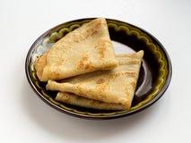 折叠在白色背景的三角鲜美薄煎饼在黑色的盘子 免版税库存照片