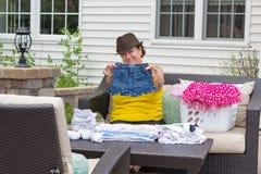 折叠她的孙女衣裳的快乐的老婆婆 免版税图库摄影