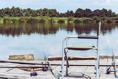 折叠椅,钓鱼的标尺在河沿的木码头 捕鱼设备的减速火箭的被定调子的图片 免版税图库摄影
