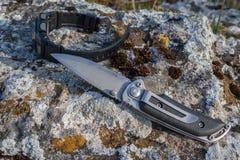 折叠的刀子和人` s手表在石头 免版税图库摄影