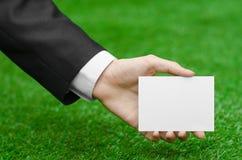 折扣和企业题目:在拿着在绿草背景的一套黑衣服的手一个白色空插件 免版税库存图片