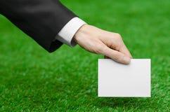 折扣和企业题目:在拿着在绿草背景的一套黑衣服的手一个白色空插件 免版税图库摄影