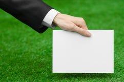折扣和企业题目:在拿着在绿草背景的一套黑衣服的手一个白色空插件 库存照片