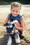 抚摸一条她的狗的小美国女孩 免版税库存照片