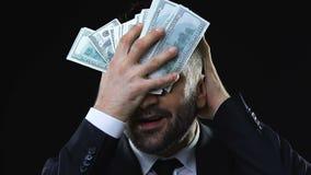抚摸与美元钞票的贪婪的商人面孔,享受财富 影视素材
