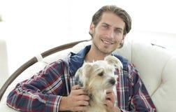 抚摸他的狗的一个微笑的人的特写镜头,当坐在一把大扶手椅子时 免版税库存图片