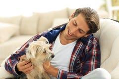 抚摸他的狗的英俊的人,当坐在一把大扶手椅子时 库存照片