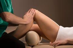 抚摸女性腿的按摩治疗师 免版税库存图片