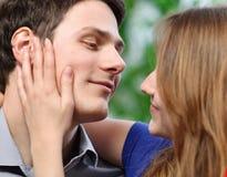 抚摸她的充满爱的男朋友的面颊俏丽的妇女 库存图片