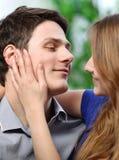 抚摸她的充满爱的男朋友的面颊俏丽的妇女 免版税库存照片