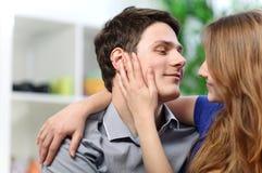 抚摸她的充满爱的男朋友的面颊俏丽的妇女 免版税图库摄影