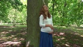 抚摸她的腹部的愉快的白种人怀孕的女孩站立在大树干附近