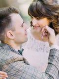 抚摸微笑的新娘的面颊的新郎的旁边特写镜头画象 免版税库存图片