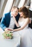 抚摸微笑的新郎的面颊的新娘的垂直的照片,当坐在餐馆时 库存照片