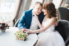抚摸新郎的面颊的新娘的浪漫画象,当坐在现代餐馆时 库存图片