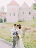 抚摸新郎的面颊的有蓝色花束的新娘的特写镜头侧视图在背景老 库存图片