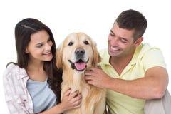 抚摸狗的爱恋的夫妇 免版税库存照片