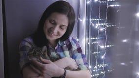抚摸猫的美丽的可爱的妇女坐用诗歌选装饰的窗台 股票视频