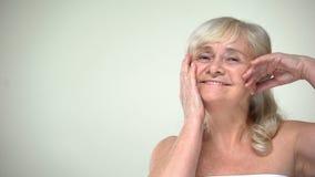 抚摸面孔微笑,skincare,正面生活态度的乐观快乐的夫人 股票视频